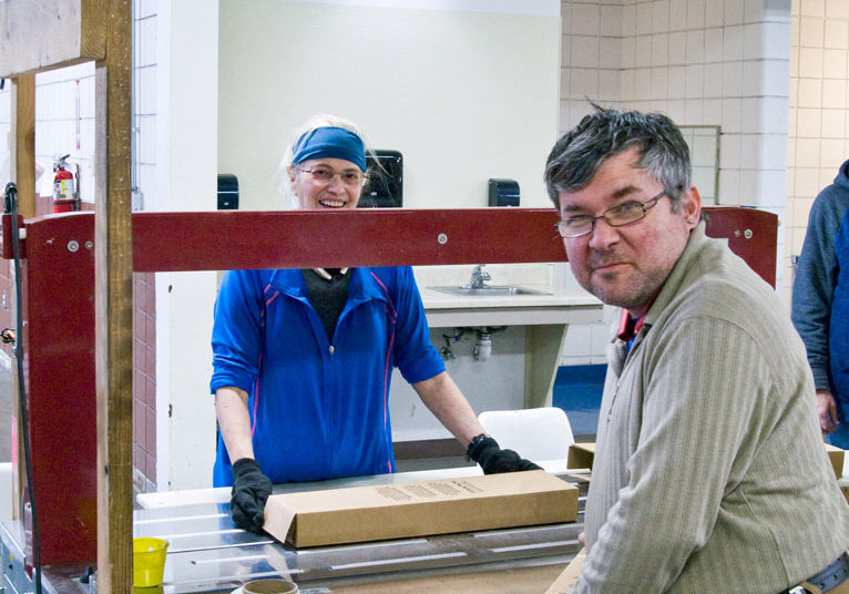 Two excited developmentally disabled employees excited and smiling while packaging and assembling at Blue Valley Industries.